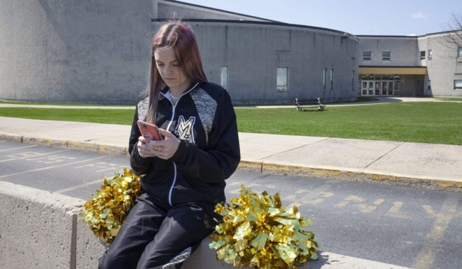 Brandi Levy is seen here wearing her former cheerleading outfit as she looks at her phone while outside Mahanoy Area High School in Mahanoy, FL.